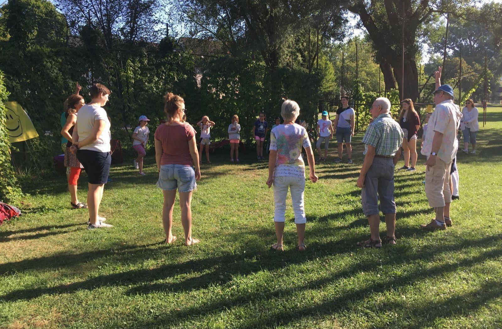 Teilnehmer des Lachyoga stehen im Garten Momo im Kreis