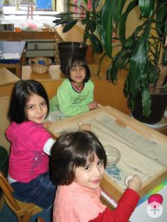 Drei Mädchen des katholischen Kindergartens Maria Königin beim experimentieren mit Sand